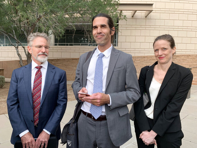 Scott Warren, center, of Ajo, Ariz. celebrates with his attorneys Amy Knight, right, and Greg Kuykendall outside court in Tucson, Ariz. on Wednesday, Nov. 20, 2019, after being acquitted of two counts of harboring in a case that garnered international attention. Prosecutors said Warren illegally helped two migrants avoid authorities. He said he was fulfilling his humanitarian duties by helping two injured men. (AP Photo/Astrid Galvan)