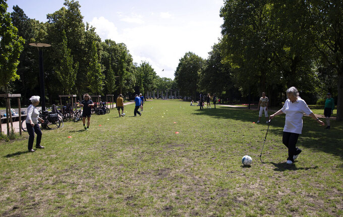 Elderly people kick a soccer ball to each other for exercise at a park in Ghent, Belgium on Friday, June 19, 2020. Belgium has lifted most of its restrictions on movement but still requires face masks on public transport and asks people to still keep a physical distance from each other, to prevent the spread of coronavirus, COVID-19. (AP Photo/Virginia Mayo)