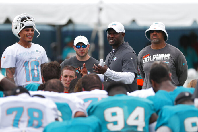 Miami Dolphins head coach Brian Flores, second from right, talks with players after the teams NFL football training camp, Monday, Aug. 5, 2019 in Davie, Fla. The Dolphins allowed a franchise record 6,257 yards in 2018, and new coach Brian Flores has brought to Miami a scheme that redefines the meanings of positions. (AP Photo/Wilfredo Lee)