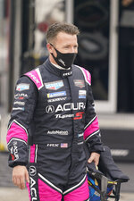 AJ Allmendinger walks back to his garage after a practice session for the Rolex 24 hour auto race at Daytona International Speedway, Saturday, Jan. 23, 2021, in Daytona Beach, Fla. (AP Photo/John Raoux)
