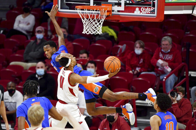 Arkansas guard Jalen Tate (11) is fouled by Florida guard Scottie Lewis (23) as he drives to the hoop during the second half of an NCAA college basketball game in Fayetteville, Ark. Tuesday, Feb. 16, 2021. (AP Photo/Michael Woods)
