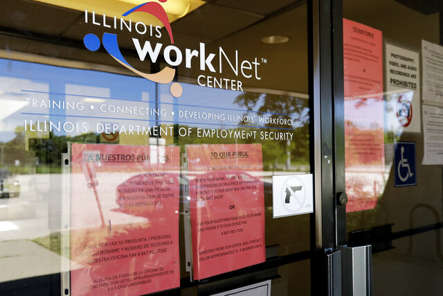 FILE - In this June 11, 2020 file photo, information signs are displayed at the closed Illinois Department of Employment Security WorkNet center in Arlington Heights, Ill. U.S. businesses sharply reduced hiring July 2020, in a sign that the resurgent viral outbreak this summer slowed the economic recovery as many states closed parts of their economies again and consumers remained cautious about spending.  (AP Photo/Nam Y. Huh)