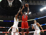 Chicago Bulls forward Cristiano Felicio (6) shoots the ball over Utah Jazz forward Derrick Favors, left, during the first half of an NBA basketball game Saturday, March 23, 2019, in Chicago. (AP Photo/David Banks)