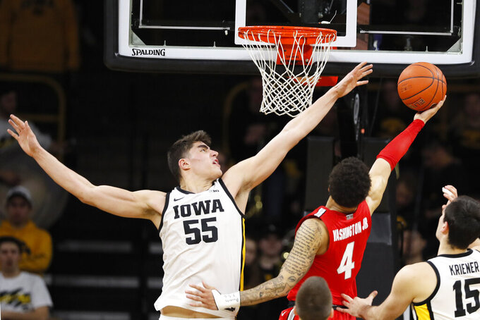 Iowa center Luka Garza (55) tries to block a shot by Ohio State guard Duane Washington Jr. (4) during the second half of an NCAA college basketball game, Thursday, Feb. 20, 2020, in Iowa City, Iowa. Iowa won 85-76. (AP Photo/Charlie Neibergall)