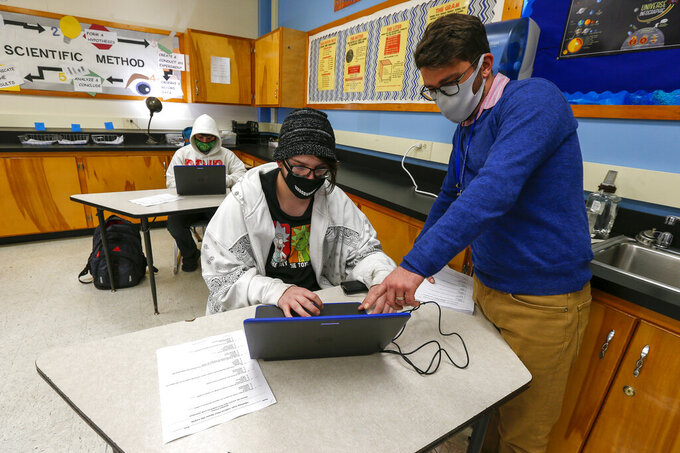 Bobby Smith gets some help opening a PowerPoint on volcanoes from QHS teacher Jared Holman at Quincy High School, Wednesday, Nov. 4, 2020. in Quincy, Ill., Wednesday, Nov. 4, 2020. (Jake Shane/Quincy Herald-Whig via AP)