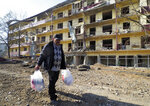 Vovik Zakharian, 72, walks past his apartment building damaged by shelling by Azerbaijan's forces during a military conflict in Shushi, outside Stepanakert, the separatist region of Nagorno-Karabakh, Thursday, Oct. 29, 2020. Fighting over the separatist territory of Nagorno-Karabakh continued on Thursday, as the latest cease-fire agreement brokered by the U.S. failed to halt the flare-up of a decades-old conflict between Armenia and Azerbaijan. (AP Photo)