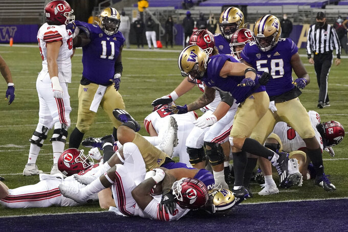 Utah running back Devin Brumfield, lower left, rushes for a touchdown against Washington during the first half of an NCAA college football game Saturday, Nov. 28, 2020, in Seattle. (AP Photo/Ted S. Warren)