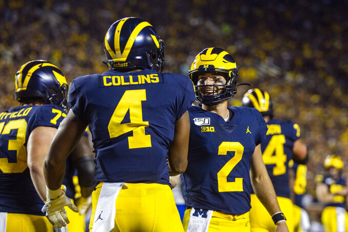 Michigan wide receiver Nico Collins (4) celebrates his touchdown with quarterback Shea Patterson (2) during the second quarter of an NCAA football game against Middle Tennessee in Ann Arbor, Mich., Saturday, Aug. 31, 2019. (AP Photo/Tony Ding)