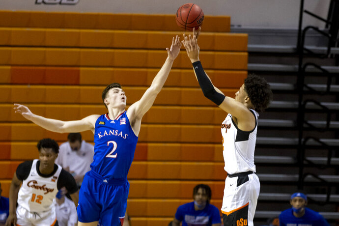 Oklahoma State's Cade Cunningham shoots over Kansas' Christian Braun during the first half of an NCAA college basketball game in Stillwater, Okla., Tuesday, Jan. 12, 2021. (AP Photo/Mitch Alcala)