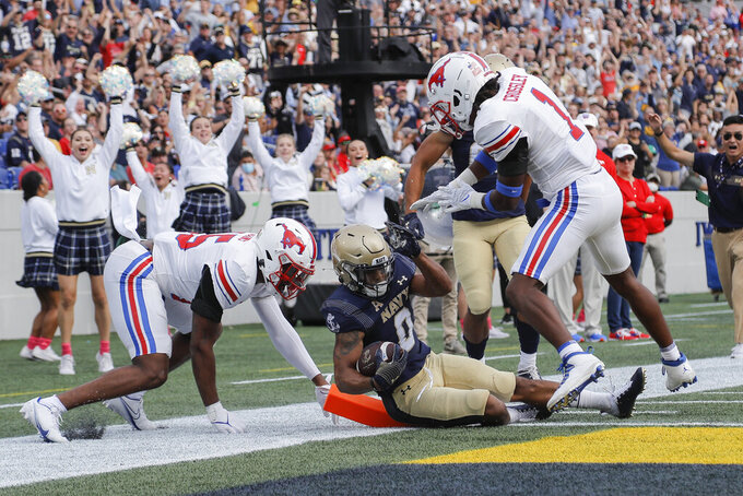 Navy fullback Chance Warren, center, scores a touchdown run as SMU linebacker Keke Burns, left, and cornerback Brandon Crossley try to stop him during the first half of an NCAA college football game, Saturday, Oct. 9, 2021, in Annapolis, Md. (AP Photo/Julio Cortez)