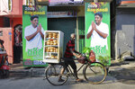 In this Wednesday, Nov. 13, 2019 photo, a Sri Lankan bread vendor pushes his bicycle past election propaganda of presidential candidate representing the governing party Sajith Premadasa in Colombo, Sri Lanka,. Sinhalese reads,