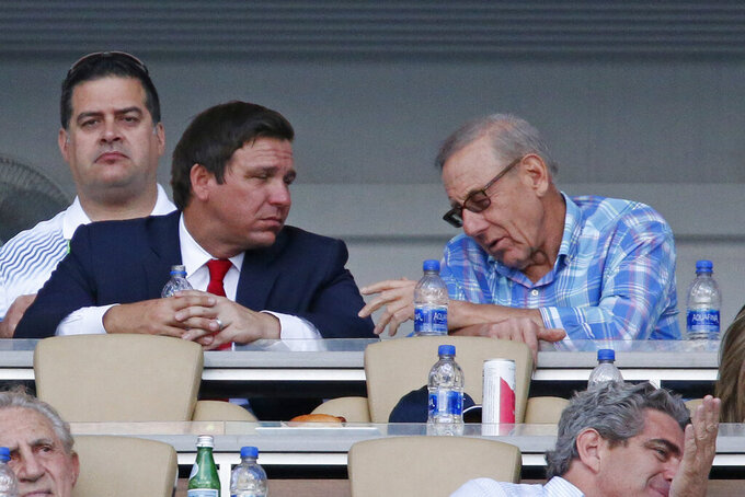 Florida Gov. Ron DeSantis, left, talks with Miami Dolphins owner Stephen M. Ross during the match between Roger Federer, of Switzerland, and Daniil Medvedev, of Russia, at the Miami Open tennis tournament, Wednesday, March 27, 2019, in Miami Gardens, Fla. (AP Photo/Joel Auerbach)