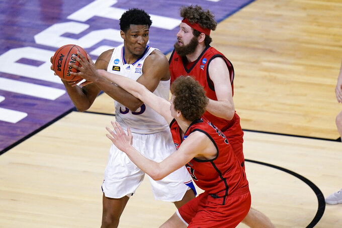 Kansas forward David McCormack, left, is pressured by Eastern Washington forward Tanner Groves, right, and teammate Eastern Jacob Groves, bottom, during the second half of a first-round game in the NCAA college basketball tournament at Farmers Coliseum in Indianapolis, Saturday, March 20, 2021. (AP Photo/AJ Mast)