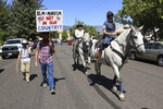 Black Lives Matter protesters are followed by counter protesters in Minden, Nev. on Aug. 8, 2020. Some Black Lives Matter supporters continued to protest after others cut short their participation in a demonstration outside the office of a northern Nevada sheriff and left amid jeers from a larger crowd of counter-protesters. Officials reported no injuries, arrests or damage as social media accounts emerged Monday, Aug. 10, 2020, about a weekend Black Lives Matter protest that was met in a small northern Nevada town by a far larger group of counter-demonstrators, including some bearing military-style weapons and tactical gear. (Jason Bean/Reno Gazette Journal via AP)