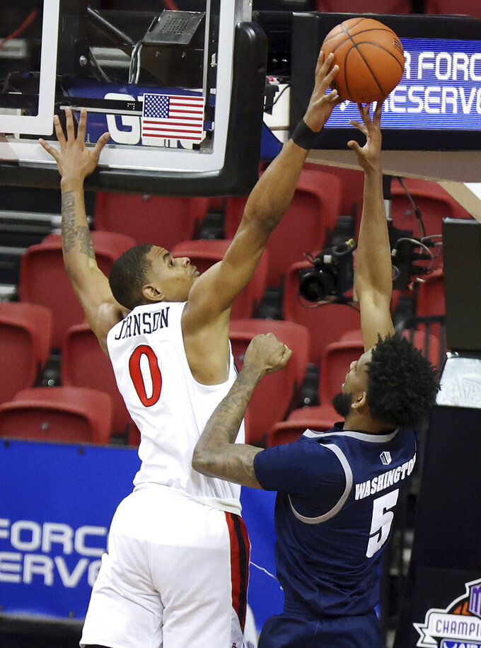 San Diego State forward Keshad Johnson (0) blocks a shot from Nevada forward Warren Washington (5) during the second half of an NCAA college basketball game in the semifinals of the Mountain West Conference men's tournament Friday, March 12, 2021, in Las Vegas. (AP Photo/Isaac Brekken)