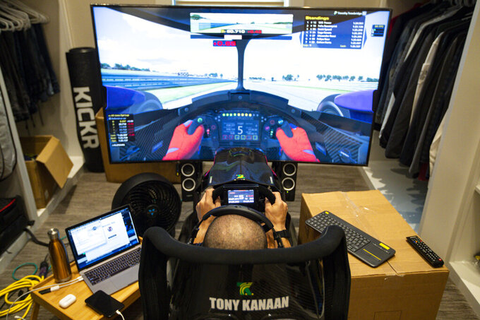 FILE - In this March 28, 2020, file photo, IndyCar driver Tony Kanaan, of Brazil,  uses a racing simulator in his home in Indianapolis to practice for a virtual racing event. As Robert Wickens fought his way back from a spinal cord injury, he kept dreaming about the day he could run against his old racing buddies. The promising Canadian driver believes he'll take his biggest step yet by making his debut in the IndyCar iRacing Challenge — a virtual race being held Saturday, April 4, 2020, on the Barber Motorsports Track in Alabama. (AP Photo/Michael Conroy, File)