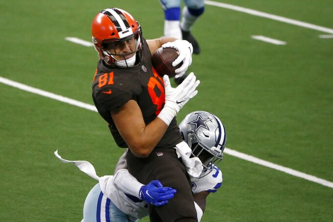 Cleveland Browns tight end Austin Hooper (81) catches a pass under pressure from Dallas Cowboys safety Donovan Wilson (37) in the first half of an NFL football game in Arlington, Texas, Sunday, Oct. 4, 2020. (AP Photo/Michael Ainsworth)