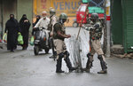 FILE-In this Aug. 10, 2019, file photo, Indian paramilitary soldiers prepare to close off a street with barbwire in Srinagar, Indian controlled Kashmir. The beautiful Himalayan valley is flooded with soldiers and roadblocks of razor wire. Phone lines are cut, internet connections switched off, politicians arrested. Narendra Modi, the prime minister of the world's largest democracy has clamped down on Kashmir to near-totalitarian levels. (AP Photo/Mukhtar Khan, file)