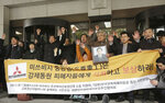 FILE - In this Nov. 29, 2018, file photo, South Korean victims of Japan's forced labor and their family members raise their hands in celebration after the Supreme Court's ruling ordering Japan's Mitsubishi Heavy Industries to compensate them in Seoul, South Korea. The modern legacy of a dark chapter in Japan's history, when hundreds of thousands of people were brought from the Korean Peninsula and other Asian nations to work in logging, in mines, on farms and in factories as forced labor, lives on in the companies that came to dominate the Japanese economy after World War II. Many of those companies are still facing demands for compensation that they say were settled by treaty decades ago.  The signs read: