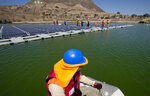 A worker on a boat approaches a floating island of solar panels at Los Bronces mine, about 65 kilometers (approximately 40 miles) from Santiago, Chile, Thursday, March 14, 2019. Los Bronces is about 3,500 meters (11,500 feet) above sea level. In 2018, the mine produced 370,000 tons of fine copper and 2,421 tons of molybdenum. (AP Photo / Esteban Felix)