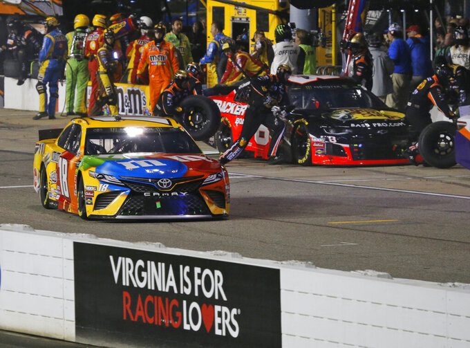 Kyle Busch (18) leaves his pit during the NASCAR Cup Series auto race at Richmond Raceway in Richmond, Va., Saturday, April 13, 2019. Busch was called for a speeding penalty on the stop. (AP Photo/Steve Helber)