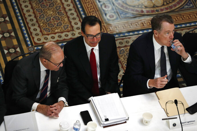 FILE- In this Feb. 21, 2019, file photo White House economic adviser Larry Kudlow, left, Treasury Secretary Steve Mnuchin, and U.S. Trade Representative Robert Lighthizer, attend a meeting of senior U.S. and Chinese officials to resume trade negotiations in Washington.  Top U.S. trade and economic officials will visit China late next week for another round of negotiations, a White House official says. Mnuchin and Lighthizer will lead the delegation, Trump administration officials say. (AP Photo/Jacquelyn Martin, File)