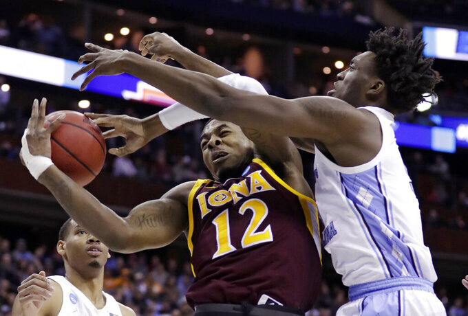 Iona's Tajuan Agee, left, and North Carolina's Nassir Little battle for a rebound in the first half during a first round men's college basketball game in the NCAA Tournament in Columbus, Ohio, Friday, March 22, 2019. (AP Photo/Tony Dejak)
