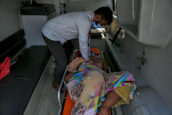 A health worker gives cardiopulmonary resuscitation (CPR) to a COVID-19 patient waiting to be attended to inside an ambulance outside a government COVID-19 hospital in Ahmedabad, India, Tuesday, April 27, 2021. The COVID-19 death toll in India has topped 200,000 as the country endures its darkest chapter of the pandemic yet. (AP Photo/Ajit Solanki)