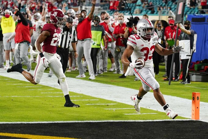 Ohio State running back Master Teague III scores a touchdown past Alabama defensive back Josh Jobe during the first half of an NCAA College Football Playoff national championship game, Monday, Jan. 11, 2021, in Miami Gardens, Fla. (AP Photo/Chris O'Meara)