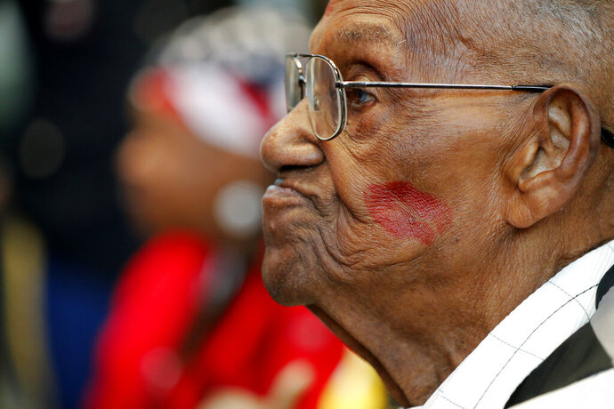 World War II veteran Lawrence Brooks sports a lipstick kiss on his cheek, planted by a member of the singing group Victory Belles, as he celebrates his 110th birthday at the National World War II Museum in New Orleans, Thursday, Sept. 12, 2019. Brooks was born Sept. 12, 1909, and served in the predominantly African-American 91st Engineer Battalion, which was stationed in New Guinea and then the Philippines during World War II. He was a servant to three white officers in his battalion. (AP Photo/Gerald Herbert)