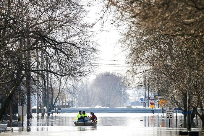 People on a boat float down floodwaters that cover Washington Street Wednesday, March 20, 2019, in Hamburg, Iowa. As some communities along the Missouri River start to shift their focus to flood recovery after a late-winter storm, residents in two Iowa cities are still in crisis mode because their treatment plants have shut down and they lack fresh water. (Chris Machian/Omaha World-Herald via AP)
