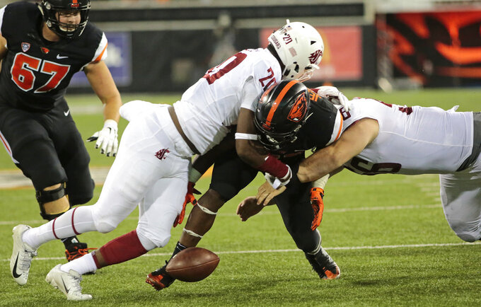 Oregon State's Jermar Jefferson, center, fumbles the ball near the end zone after taking a hit from Washington State's Dominick Sivlels (20) and Taylor Comfort, right, during the fourth quarter of an NCAA college football in Corvallis, Ore., Saturday, Oct. 6, 2018. (AP Photo/Timothy J. Gonzalez)
