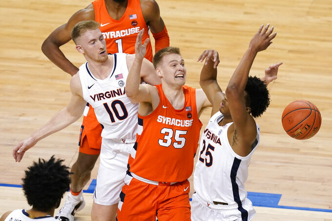 Virginia forward Sam Hauser (10) along with teammate guard Trey Murphy III (25) fight for a rebound with Syracuse guard Buddy Boeheim (35) during the first half of an NCAA college basketball game in the quarterfinal round of the Atlantic Coast Conference tournament in Greensboro, N.C., Thursday, March 11, 2021. (AP Photo/Gerry Broome)
