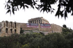 Members of Greece's Communist Party stand on the ancient Acropolis Hill over giant banners protesting against the Prespa Agreement in front of the ancient Parthenon temple, in Athens Thursday, Jan. 24, 2019. Greek lawmakers are debating a historic agreement aimed at normalizing relations with Macedonia in a stormy parliamentary session scheduled to culminate in a Thursday vote, while opponents have announced a series of protests. (AP Photo/Petros Giannakouris)