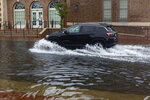 A sport utility vehicle moves down a flooded street in Ventnor, N.J., Friday, July 10, 2020. Fast-moving Tropical Storm Fay made landfall in New Jersey on Friday amid heavy, lashing rains that closed beaches and flooded shore town streets. (Kristian Gonyea/The Press of Atlantic City via AP)