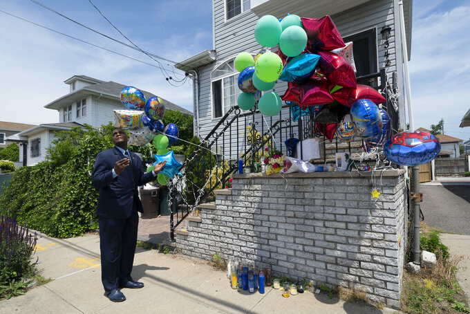 Minister Isaac Mickens says a prayer at a memorial for ten-year-old Justin Wallace, Tuesday, June 8, 2021 in the Far Rockaway neighborhood of New York. The boy was killed and his 29-year-old uncle was wounded by a gunman at a family barbecue, Saturday, June 5. The Democratic primary race for New York City mayor is nearing the finish line with a surge in shootings pushing public safety to the top of some voters' concerns. (AP Photo/Mark Lennihan)