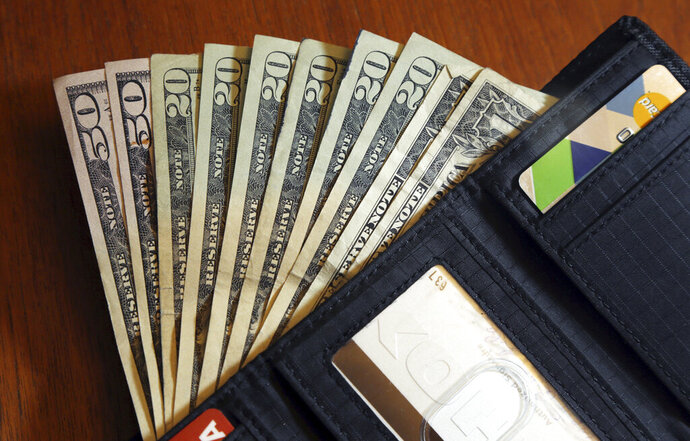 FILE - In this June 15, 2018 file photo, cash is fanned out from a wallet in North Andover, Mass.  Only 33% of American adults follow a budget, according to an October 2017 survey of Americans from NerdWallet . The time and effort involved are often cited as the reasons, but trying and failing is also a barrier. (AP Photo/Elise Amendola, File)