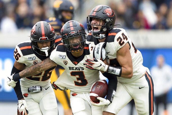 Oregon State  defensive back David Morris (24) and defensive back Jojo Forest (26) react after defensive back Jaydon Grant (3) intercepted a pass intended for California  wide receiver Nikko Remigio, not seen, in the fourth quarter of an NCAA college football game in Berkeley, Calif., Saturday, Oct. 19, 2019. Oregon St. won 21-17. (AP Photo/John Hefti)