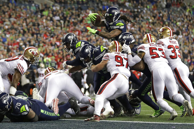 Seattle Seahawks running back Marshawn Lynch, top, leaps to score a touchdown against the San Francisco 49ers during the second half of an NFL football game, Sunday, Dec. 29, 2019, in Seattle. The 49ers won 26-21. (AP Photo/Ted S. Warren)