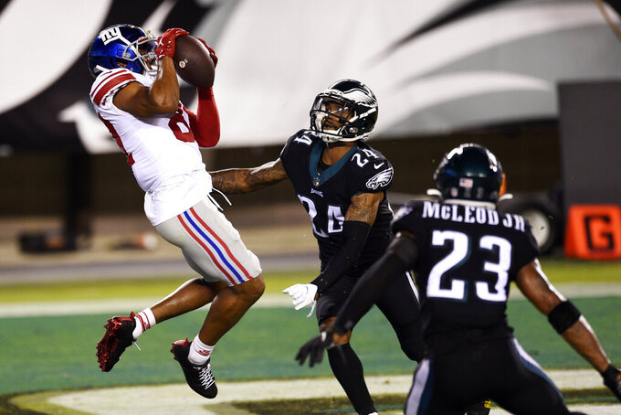 New York Giants' Sterling Shepard (87) catches a touchdown pass against Philadelphia Eagles' Darius Slay (24) and Rodney McLeod (23) during the second half of an NFL football game, Thursday, Oct. 22, 2020, in Philadelphia. (AP Photo/Derik Hamilton)