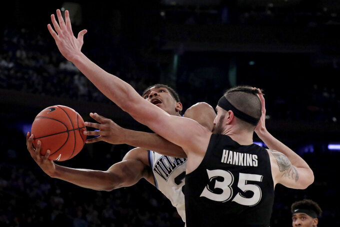 Villanova forward Jermaine Samuels, left, goes up for a shot against Xavier forward Zach Hankins during the first half of an NCAA college basketball semifinal game in the Big East men's tournament, Friday, March 15, 2019, in New York. (AP Photo/Julio Cortez)