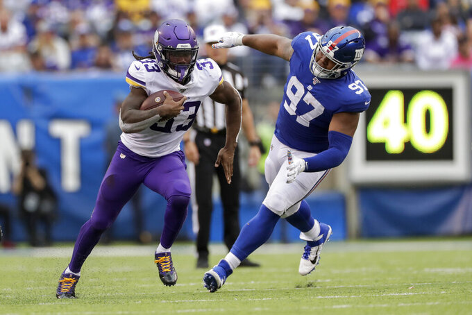 Minnesota Vikings running back Dalvin Cook (33) runs the ball against New York Giants defensive tackle Dexter Lawrence (97) during the third quarter of an NFL football game, Sunday, Oct. 6, 2019, in East Rutherford, N.J. (AP Photo/Adam Hunger)