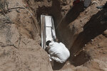 A worker wearing a protection suit against the spread of the new coronavirus buries a coffin in an area of the San Rafael municipal cemetery set apart for COVID-19 cases in Ciudad Juarez, Mexico, Tuesday, May 19, 2020. (AP Photo/Christian Chavez)