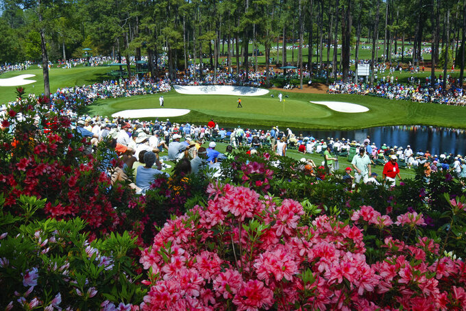 FILE - In this April 4, 2011, file photo, golf fans watch on the par three 16th hole during a practice round for the Masters at Augusta National Golf Club in Augusta, Ga. For the first since a three-year suspension caused by World War II, this tradition unlike any other won't be held in its usual slot on the calendar, where it serves as sort of an unofficial kickoff to spring. (Tim Dominick/The State via AP, File)