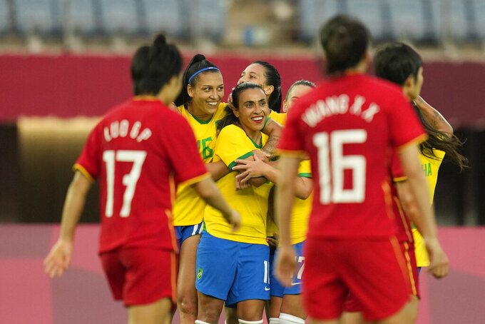 Brazil's Marta, center, celebrates scoring her side's 3rd goal against China during a women's soccer match at the 2020 Summer Olympics, Wednesday, July 21, 2021, in Rifu, Japan. (AP Photo/Andre Penner)