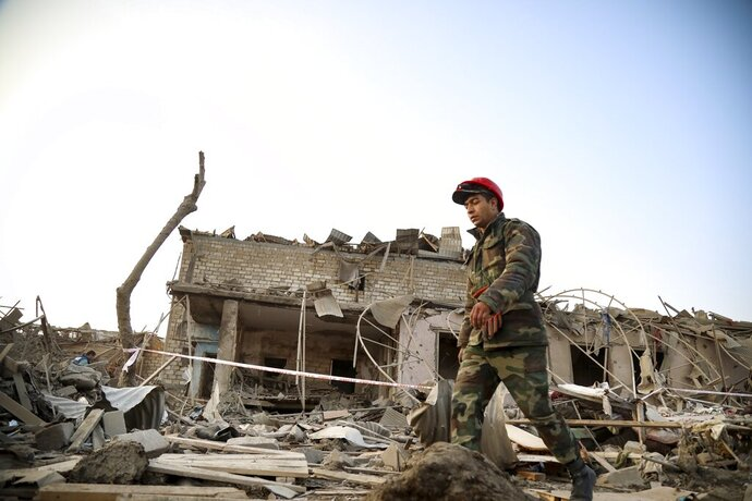 A soldier walks past a destroyed house in a residential area that was hit by rocket fire overnight by Armenian forces, early Saturday, Oct. 17, 2020, in Ganja, Azerbaijan's second largest city, near the border with Armenia. Azerbaijan has accused Armenia of striking its second-largest city with a ballistic missile that killed at least 13 civilians and wounded 50 others in a new escalation of their conflict over Nagorno-Karabakh. (AP Photo/Aziz Karimov)