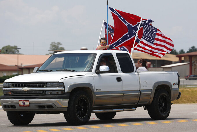 FILE - In this  June 21, 2020, file photo, race fans fly Confederate battle flags and a United States flag as they drive by Talladega Superspeedway prior to a NASCAR Cup Series auto race in Talladega, Ala. The Confederate battle flag is losing its place of official prominence in the South 155 years after the end of the Civil War. NASCAR, has banned the rebel banner from its car races. (AP Photo/John Bazemore, File)