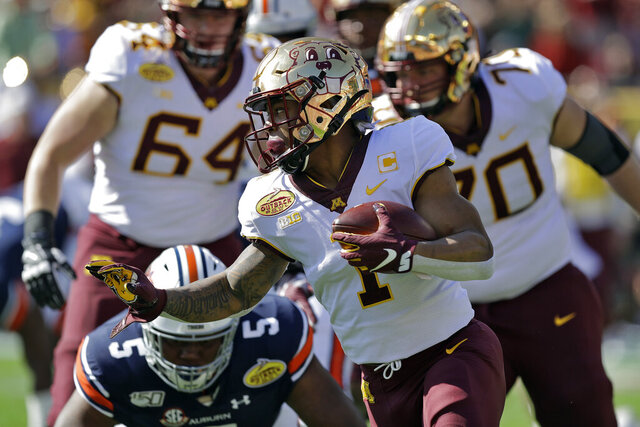 Minnesota running back Rodney Smith (1) runs past Auburn defensive tackle Derrick Brown (5) during the first half of the Outback Bowl NCAA college football game Wednesday, Jan. 1, 2020, in Tampa, Fla. (AP Photo/Chris O'Meara)