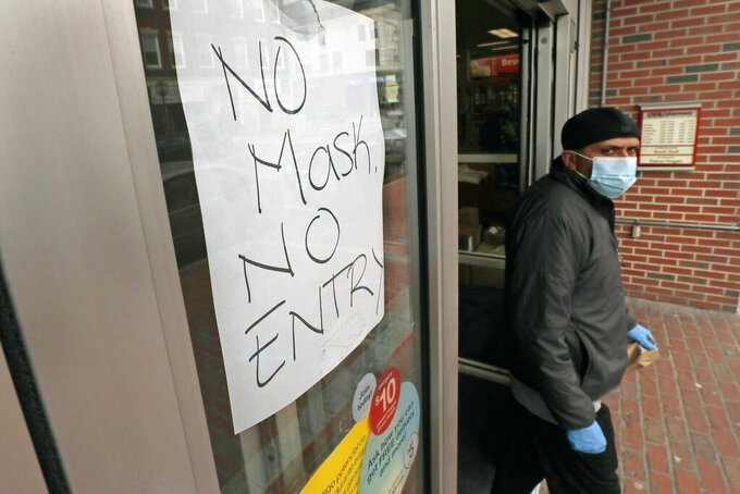 FILE - In this April 28, 2020, file photo, a masked shopper walks past a sign taped to the front door of a CVS Pharmacy, requesting patrons wear masks if they intend on shopping inside due to the COVID-19 virus outbreak, in Chelsea, Mass. Workers are being asked to get shoppers to follow new social distancing protocols like adhering to one-way aisles, keeping their masks on and staying six feet away from others to keep everyone safe. (AP Photo/Charles Krupa, File)