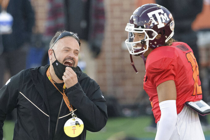 American Team head coach Matt Rhule (Carolina Panthers) jokes with American Team quarterback Kellen Mond of Texas A&M (12) during the American Team practice for the NCAA Senior Bowl college football game in Mobile, Ala., Thursday, Jan. 28, 2021. (AP Photo/Matthew Hinton)